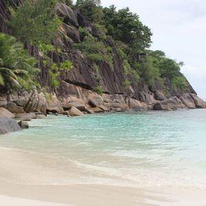 Four Seasons Resort Seychelles Luxury Seychelles holiday Packages Man Strolling On Beach